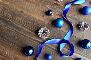 ブルーのクリスマスオーナメントとリボン 黒木材背景の写真素材 [FYI00893230]