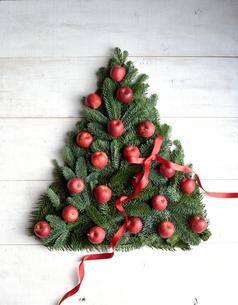 林檎と赤いリボンのクリスマスツリー 白木材背景の写真素材 [FYI00893555]