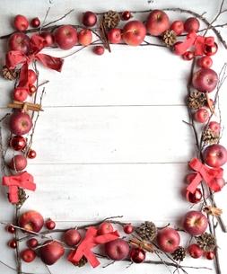 林檎と赤いリボンとクリスマス飾りのフレーム 白木材背景の写真素材 [FYI00893933]