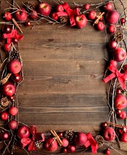 林檎とシナモンスティックと赤いクリスマス飾りのフレーム 黒木材背景の写真素材 [FYI00893948]