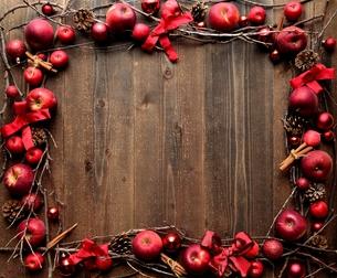 林檎とシナモンスティックと赤いクリスマス飾りのフレーム 黒木材背景の写真素材 [FYI00893950]