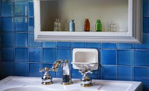洗面所の壁の青色のタイルと棚の小瓶の写真素材 [FYI00894106]