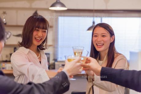 仲間と笑顔で乾杯する若い女性の写真素材 [FYI00894399]