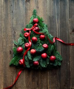 林檎とモミの葉のクリスマスツリー 黒木材背景の写真素材 [FYI00894605]