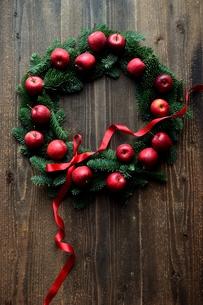 林檎とモミと赤いリボンのクリスマスリース 黒木材背景の写真素材 [FYI00894619]