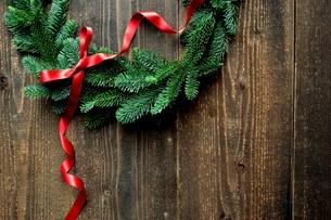 モミと赤いリボンのクリスマスリース 黒木材背景の写真素材 [FYI00894622]