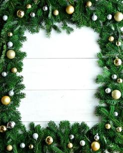 金色系ののクリスマス飾りとモミの葉のフレームの写真素材 [FYI00894828]