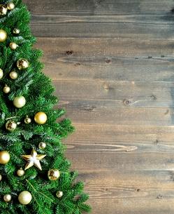 金色の星型のクリスマス飾りとクリスマスツリー 黒木材背景の写真素材 [FYI00894843]