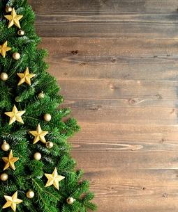 金色の星型のクリスマス飾りとクリスマスツリー 黒木材背景の写真素材 [FYI00894844]