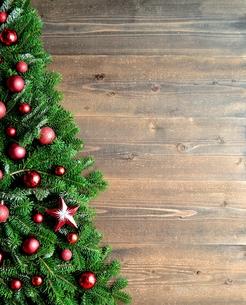 赤いクリスマス飾りとクリスマスツリー 黒木材背景の写真素材 [FYI00894845]