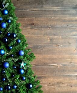 青いクリスマス飾りとクリスマスツリー 黒木材背景の写真素材 [FYI00894846]