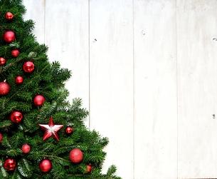 赤いクリスマス飾りとクリスマスツリー 白木材背景の写真素材 [FYI00894871]
