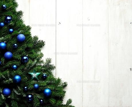 ブルーのクリスマス飾りとクリスマスツリー 白木材背景の写真素材 [FYI00894872]