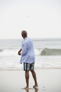 Man throwing stone into lake (rear view)の素材 [FYI00899480]