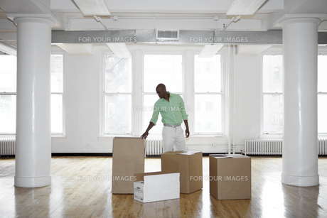 Man unpacking boxes in empty officeの素材 [FYI00899506]