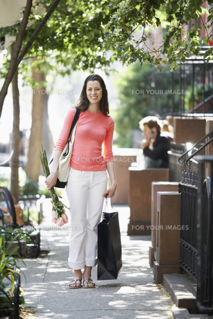 woman with bags and roses on sidewalkの素材 [FYI00899557]
