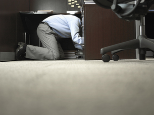 Male office worker kneeling under deskの素材 [FYI00899970]