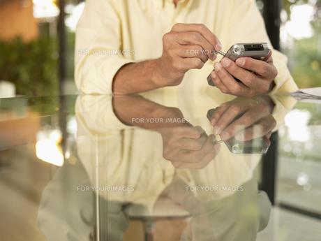 Man using PDA (close-up)の素材 [FYI00899987]