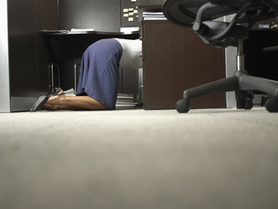 Female office worker kneeling under deskの素材 [FYI00899995]