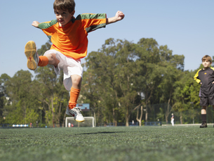 Boy kicking in soccer fieldの素材 [FYI00900030]