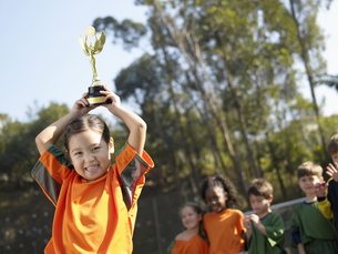 Girl holding trophy, and soccer teamの素材 [FYI00900047]