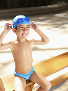 Boy in swimming trunks adjusting gogglesの素材 [FYI00900049]