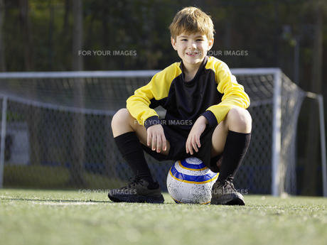 Young boy sitting on soccer ballの素材 [FYI00900054]