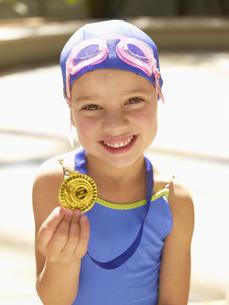 Girl in swimming costume holding medalの素材 [FYI00900059]