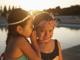 Girls sharing secret by swimming poolの素材 [FYI00900062]