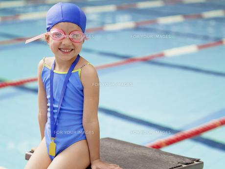 Girl wearing swimming goggles by poolの素材 [FYI00900069]