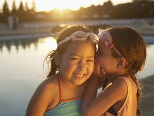 Girls sharing secret by swimming poolの素材 [FYI00900070]