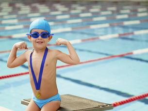 Boy celebrating medal by swimming poolの素材 [FYI00900092]