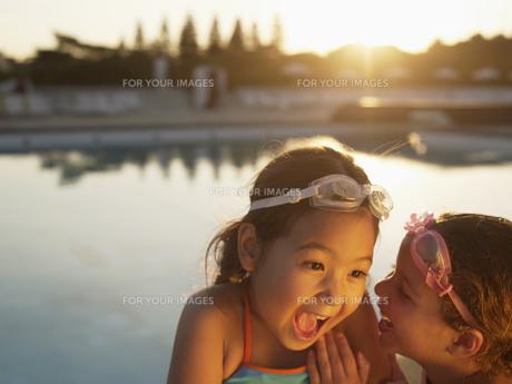 Girls sharing secret by swimming poolの素材 [FYI00900103]