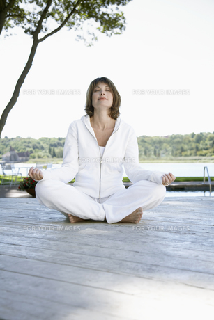 Woman meditating on deckの素材 [FYI00900219]