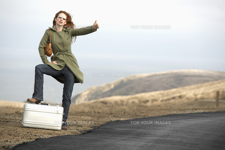 Woman hitchhiking with metal briefcaseの素材 [FYI00900466]