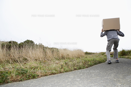 Man carrying cardboard box on roadの素材 [FYI00900467]