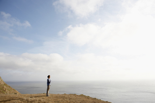 Man standing on cliff by oceanの素材 [FYI00900488]