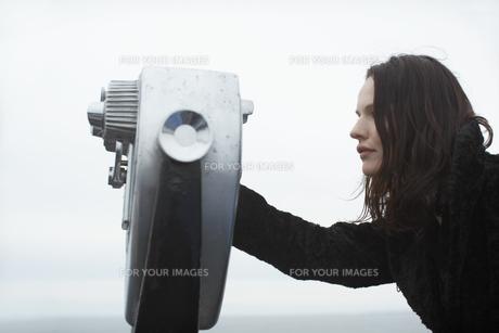 Young woman looking through binocularsの素材 [FYI00900535]