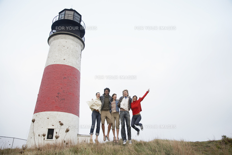 Five people jumping by lighthouseの素材 [FYI00900678]