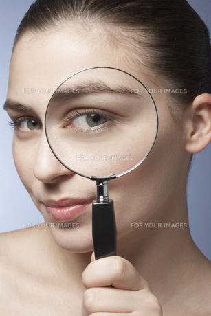 Woman looking through magnifying glassの素材 [FYI00900766]