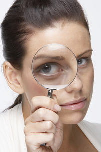Woman looking through magnifying glassの素材 [FYI00900779]