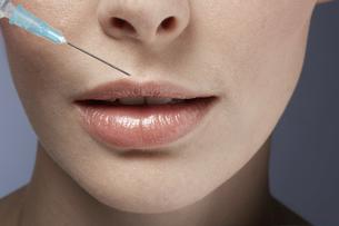 Syringe near womans lipsの素材 [FYI00900792]