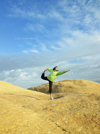 Woman doing yoga on rocky landscapeの素材 [FYI00901096]