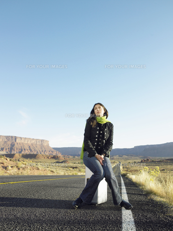 Woman hitchhiking on rural roadの素材 [FYI00901103]