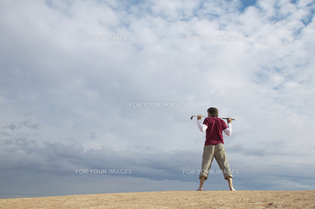 Man with golf club standing on rockの素材 [FYI00901115]