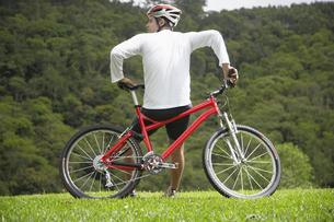Mid adult man leaning on mountain bikeの素材 [FYI00901336]
