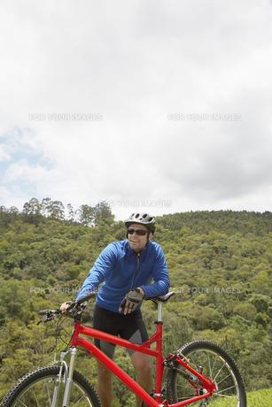 Male cyclist leaning on mountain bikeの素材 [FYI00901432]