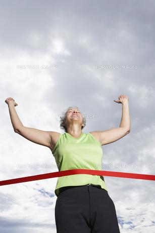 Female runner crossing finishing lineの素材 [FYI00901665]