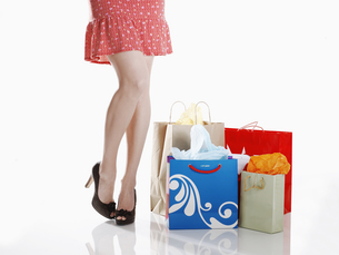 Woman standing by shopping bagsの素材 [FYI00901829]