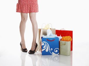 Woman standing by shopping bagsの素材 [FYI00901857]
